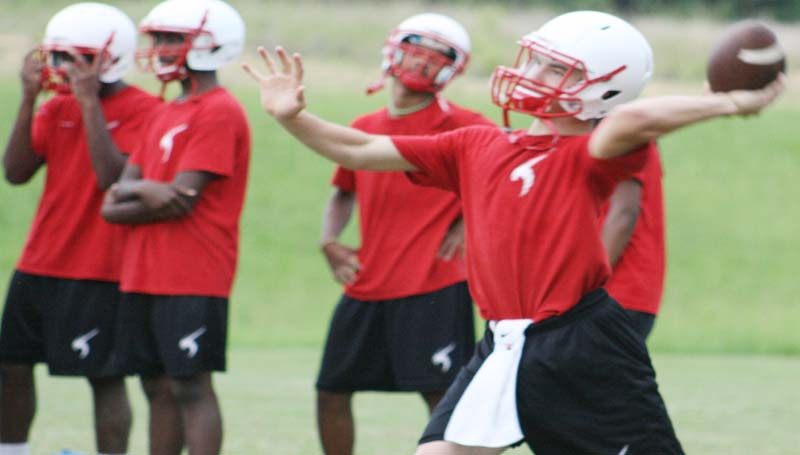 DAILY LEADER / MARTY ALBRIGHT / Loyd Star's quarterback Parker Flowers works on his throwing technique with his receivers.