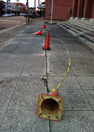 DAILY LEADER / Cones and caution tape have been placed along the sidewalk in front of the downtown Post Office.