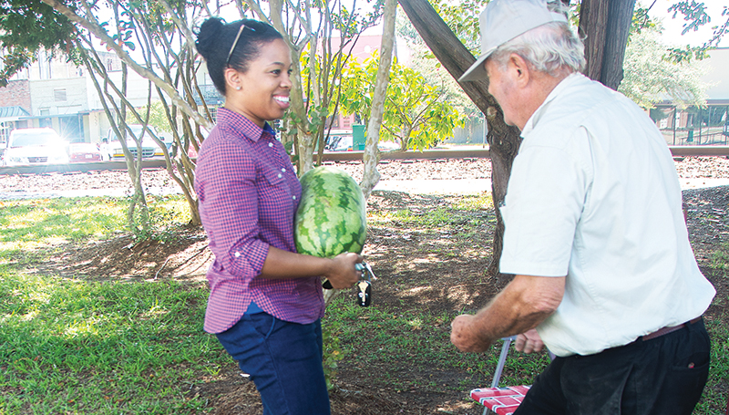 DAILY LEADER / KATIE WILLIAMSON / Ashley Tucker buys a watermelon from Delton Moak in Railroad Park Friday on the last day of the Brookhaven Farmer's Market this summer.