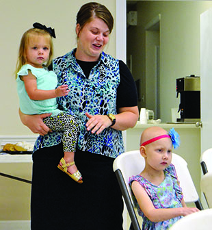 As daughter Kalie Wilkerson, (above right) 7, listens, her mother Jessica Wilkerson, holding 2-year-old Jolie, talks about how much Kaley's Make-A-Wish Disney trip meant for their family.