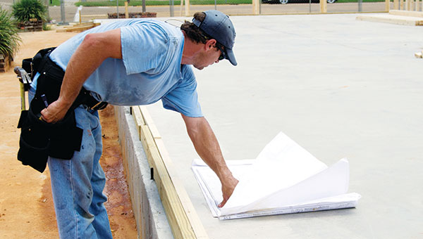 DAILY LEADER / RACHEL EIDE / Bubba Dooley, with DWD Construction, reviews the plans before starting work on the north wall Tuesday afternoon.