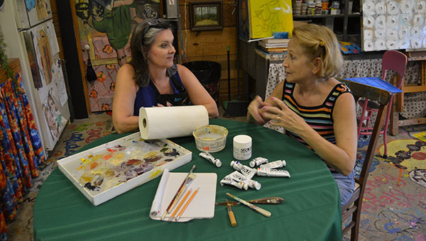 DAILY LEADER / RACHEL EIDE / Ava Jane Newell (from left) and Sue Minter talk Wednesday afternoon in The Art Barn about plans for painting workshops planned for Oct. 24-25. All paints and media will be provided to registered participants, and artists need only bring a few personal supplies such as the items displayed on the table. The workshops are jointly sponsored by The Art Barn and Brookhaven Regional Arts Guild.