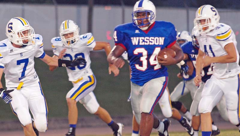 DAILY LEADER / TRACY FISCHER / Wesson's Arthur Harris (34) outruns Sumrall defenders Rhett Harvey (7), Jacob Phelps (28) and Grant Baxter (41) for a huge gain Friday night at Stone Stadium.