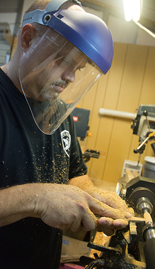 Sheriff Steve Rushing turns a pen on the small lathe in his home workshop Thursday night.