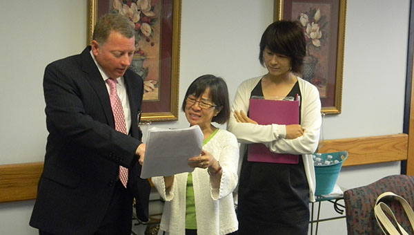 PHOTO SUBMITTED / William Gates, director of the Mississippi Adolescent Center in Brookhaven, (from left) discusses the services provided by the center with Yukari Ogita, member of the Osaka Prefectural Assembly, Health and Welfare Committee, of Japan, as her translator looks on. The Japanese visitors toured the local center earlier this month.