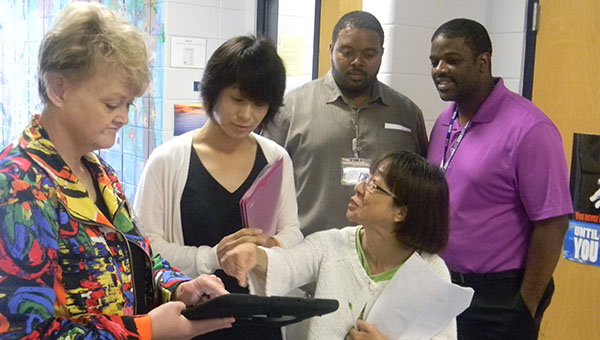 PHOTO SUBMITTED / Donna Horton, director of client services at Mississippi Adolescent Center in Brookhaven, demonstrates a program called Talking Tiles with Yukari Ogita, member of the Osaka Prefectural Assembly, Health and Welfare Committee, of Japan, and her translator during a recent visit to the local facility. Looking on are Eric Brown, director of staff development at MAC, and Bobby Alsworth, principal of MAC.
