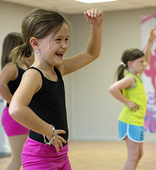 DAILY LEADER / KATIE WILLIAMSON / Bryleigh Garner, 7, can't help but giggle a bit while learning dance moves in the Brookhaven Dance Academy ballet class Wednesday at the Brookhaven Recreation Center.