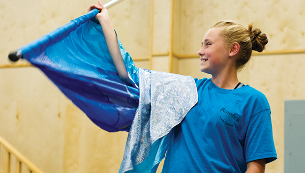 DAILY LEADER / KATIE WILLIAMSON / Natalie Lynn, 13,  laughs as she practices flag twirling during Loyd Star color guard practice.