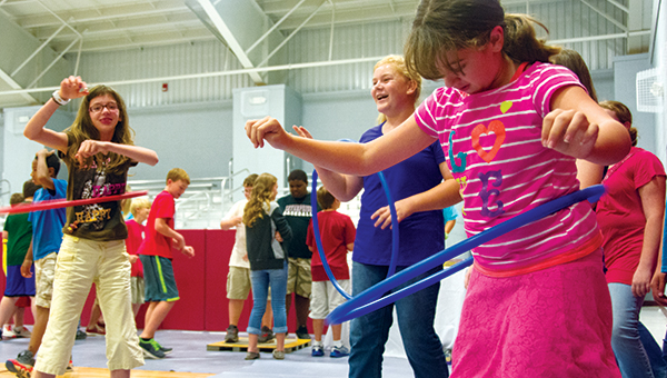 DAILY LEADER / KATIE WILLIAMSON / The Brookhaven Junior Auxiliary hosted a health fair at Enterprise School Wednesday to teach children about the importance of a healthy diet, daily exercise and good hygiene. Chloe McCormick, 13, (from left) Molly Thompson, 11, and Jacy Jordan, 12, hula hoop during the exercise portion of the health fair.