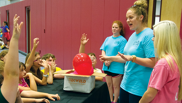 DAILY LEADER / KATIE WILLIAMSON / Meanwhile, JA member Juliana Adams  teaches children about the effects of diet and exercise on a heart using differently inflated balloons to illustrate the difference between a health person and unhealthy person.