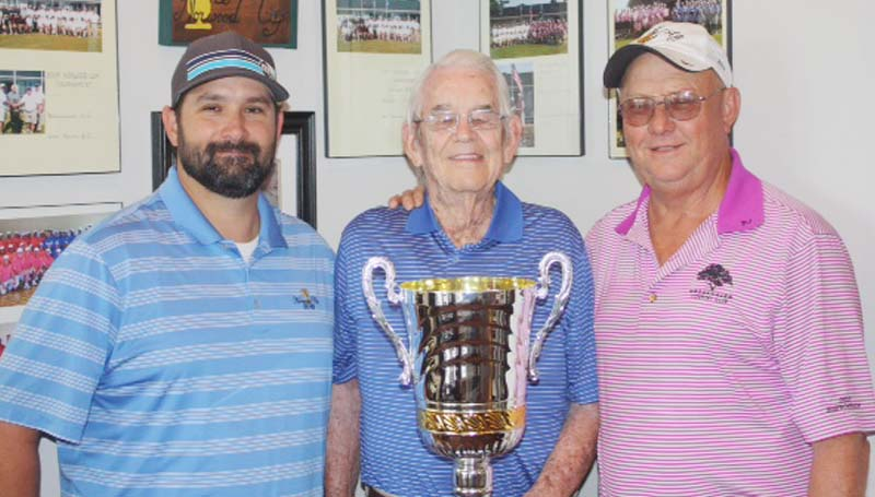 DAILY LEADER / Photo Submitted / Wolf Hollow Club team captain Alex Shoemake (left), and Brookhaven Country Club team captain Glynn Murray (right) gladly pose with Mr. Ed Norwood and his Cup as they get ready to lead their teams to victory this weekend. Competition begins Saturday morning at 10 with a nine-hole, alternate shot format. After lunch, a four-ball match play tournament will be held at the Wolf Hollow Golf Club, starting at 1 p.m. 	Individual matches are set for Sunday at the Brookhaven Country Club, beginning at 1 p.m.