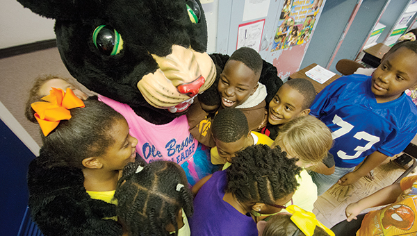 DAILY LEADER / KATIE WILLIAMSON / Polly the Panther gets hugged by Brookhaven Elementary School teacher Samantha Rushing's third-grade class during the read like a champion event Friday.