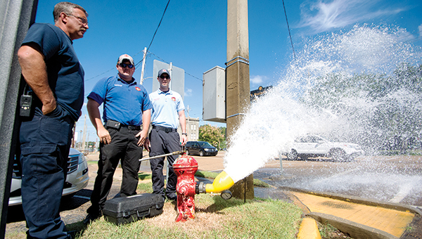 DAILY LEADER / KATIE WILLIAMSON / Brookhaven Fire Captain Mark Porter, Firefighter Garrette Case and fire lieutenant Rhett Case open a fire hydrant in downtown Brookhaven.  Fire Chief Tony Weeks said they open every plug twice a year to flush out sediment and rocks that could damage the fire truck water pumps or clog the hydrants. He said firemen are also trimming any foliage that may have built up around the hydrants to make the units are more visible. Hydrants will be opened across town for the next few months until each plug is tested. There are over 800 total hydrants in Brookhaven, and each one will be opened for ten minutes until the dirty water is flushed out.