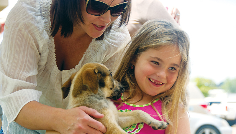 DAILY LEADER / KATIE WILLIAMSON / April Case helps her daughter Emma Case, 6, hold a puppy at the BARL/Copiah Animal Shelter adoption event at Pet Sense Sunday.
