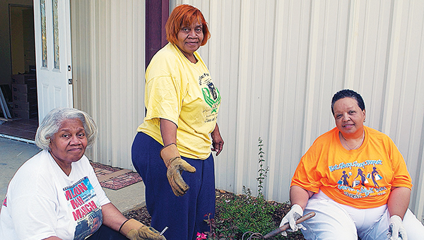 DAILY LEADER / PRISCILLA LOEBENBERG / Mamie Banks (left), Blanche Cason and Glenda Bryant work  landscaping Thursday at Kynett United Methodist Church in preparation for a ceremony celebrating the rebuilding of the church's sanctuary on Sunday.