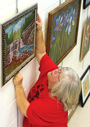 DAILY LEADER / KATIE WILLIAMSON / Debbie Whittington hangs a picture of sunflowers painted by Miranda Moak Wednesday afternoon at the Lincoln-Lawrence-Franklin Regional Library.