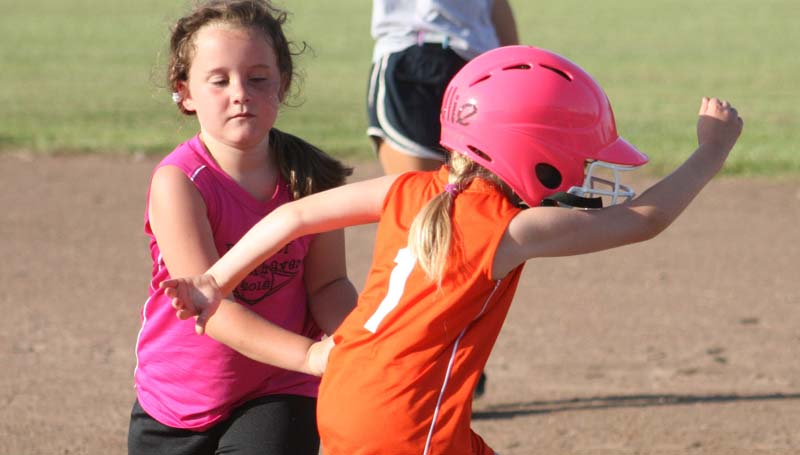 Bank of Brookhaven's Mylane Newman (left) tags out Southern Graphics runner Allie Shleton.