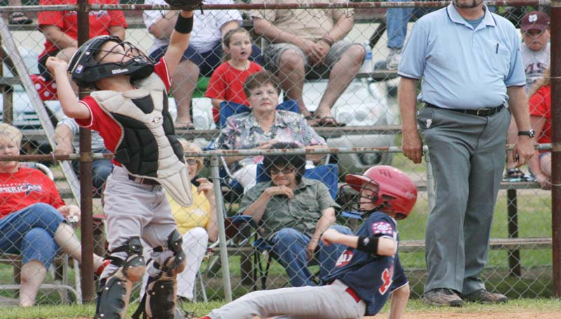 DAILY LEADER / MARTY ALBRIGHT / Lincoln County Americans' catcher Brayden Livings leaps to make the catch as Lincoln County National runner Matthew Newman slides in safely at home plate Monday at Keystone Park.