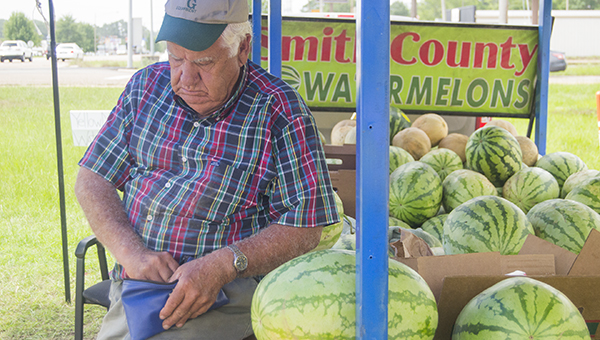 Nathaniel Weathersby / Darrell Wilson deposits the results of another sale at his watermelon stand at the intersection of US Highway 51 and Union Church Road. Wilson sells yellow and red watermelons from a farm in Smith County. He also sells cantaloupes, tomatoes and other fruit.
