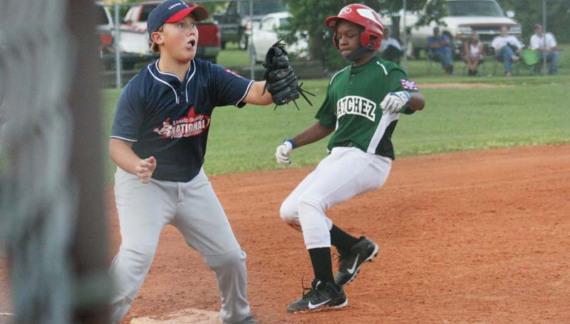 DAILY LEADER / MARTY ALBRIGHT / Lincoln County Nationals third baseman Trenton Tarver waits on the throw from home plate as Natchez runner Christian Wright steals third safely on a pass ball Tuesday night in Dixie Youth AAA action at Keystone Park.