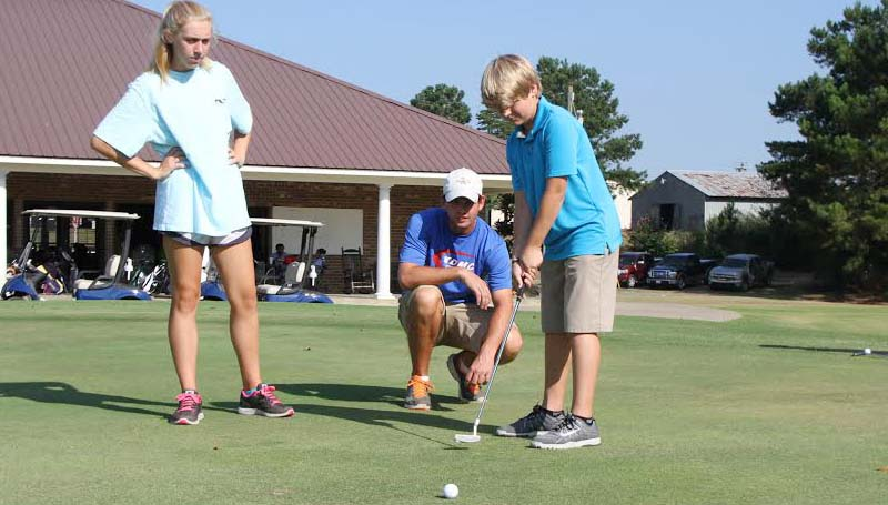 CO-LIN MEDIA / NATALIE DAVIS / Brayden Luper of Brookhaven putts while junior golf camp instructors Olivia Ross and Will Lee look on.