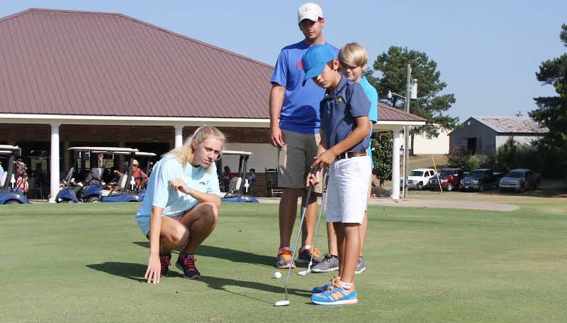 DAILY LEADER / NATALIE DAVIS / Junior golf camp instructors Olivia Ross and Will Lee and camper Brayden Luper watch as Conner Reed of Brookhaven practices his putting stroke.