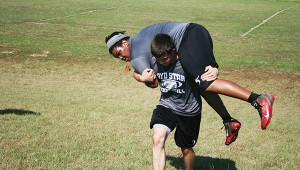 Loyd Star's junior quarterback Parker Flowers works on his strength as he carries teammate Terrance Fields up the hill during a fireman carry exercise.