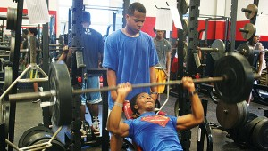 Montero Martin performs an incline brench press while teammate Trey Murray looks on during Brookhaven's summer workout.