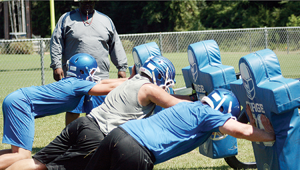 Photos by MARTY ALBRIGHT Brookhaven Academy's linemen Carter Culbertson (right), Roger Rushing (middle) and J.T. Cline practices their blocking skills as Coach Jesse Bowman looks on Friday.