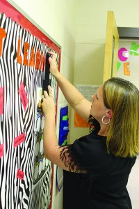 """Hart staples a letter onto a board of decorations about """"love of learning"""". Hart encourages parents to establish a routine bedtime and make sure students are eating breakfast."""