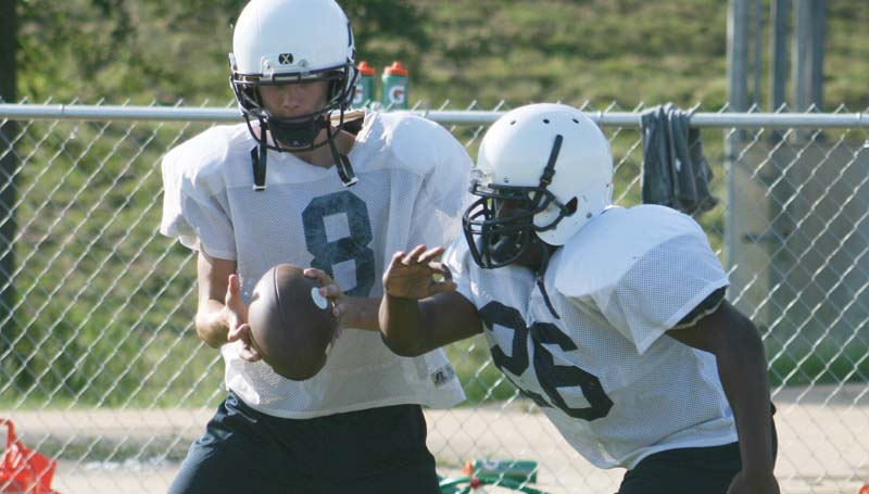 DAILY LEADER / MARTY ALBRIGHT / Bogue Chitto quarterback Trey Nettles hands off the ball to runningback Chris Taylor  as the Bobcats worked on some offensive drills.