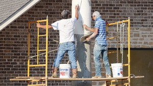 Photo by Luke Horton A crew works on the front columns of the New Zion Church of God in Christ building on Union Street Tuesday morning. New Zion COGIC started in 1952 with the construction of a brush arbor on land in Caseyville.  The new church building is expected to open soon.