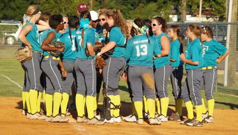DAILY LEADER / Jana Harp / Lawrence County's softball players huddles around first base to receive some instruction from their coach Meleah Howard Thursday at Mendenhall.