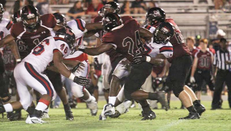 Daily Leader / April Clopton / Brookhaven's Wesley Calcote (7) and Greg Watts (46) works together to bring down Lawrence County running back Quitten Brown (24) Friday night in Monticello.