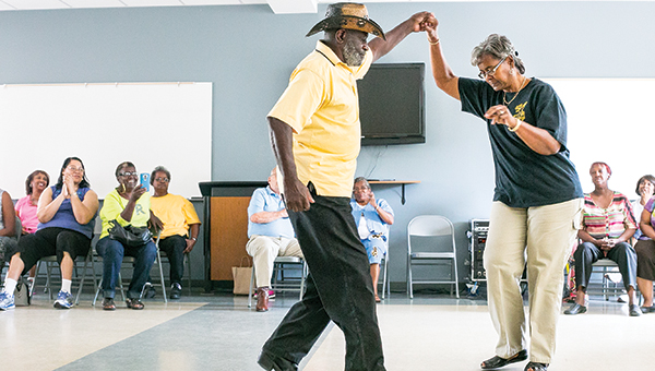 Photo by Julia V. Pendley Kirby Humphries and Willie Ann Benjamin show off their moves with an old-fashioned swing-out dance from the 1960s during a talent show at the Jimmy Furlow Senior Center Thursday. The show included singing, modeling, skit performance, dancing and more.  Over 50 people attended what was a lively, fun and energized event.