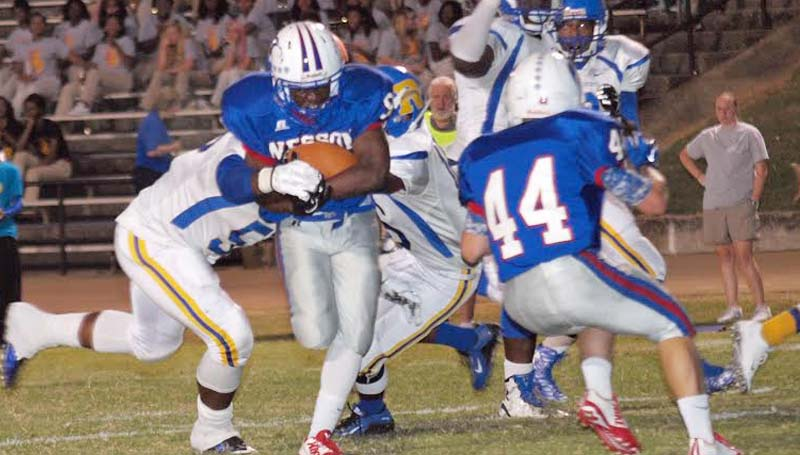 Daily Leader / Tracy Fischer / Wesson running back Cornelius Barlow (9) clutches the ball the as Raymond's defenders Jemerio Washington (5) and Preston McGowan Jr. (16) tries to strip it from behind Friday night at Stone Stadium.