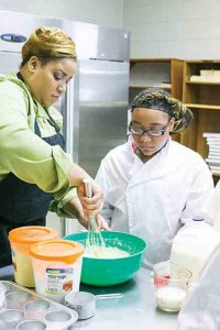Culinary arts teacher Kristen Williams shows students how to make cornbread on Friday. The program is partnered with the National Restaurant Association's Pro Start Program to give students an edge on the competition in a diverse culinary field.