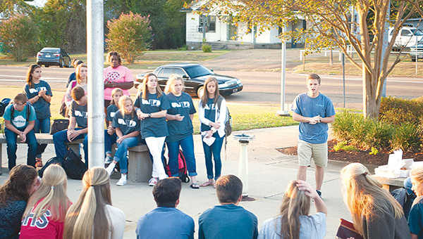 Photos by Julia V. Pendley  FCA President Taylor Pendley address a crowd of about 80 during the annual See You at the Pole event Wednesday morning at BHS.
