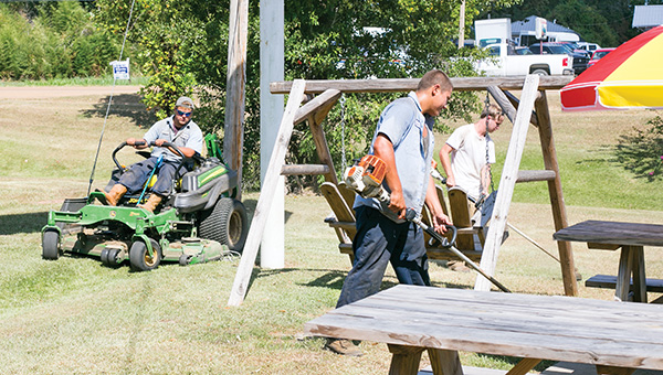 Employees of U.S. Lawns in Brookhaven will enjoy Labor Day off this year, while Labor Day 2014 came and went with work as usual. From left, Sean White, Levi Forsyth and Nick King (in white) do some landscape maintenance at a snowball stand on Highway 51.