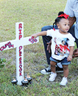 Richardson's young niece lays a hand on their memorial marker where the fatal wreck occurred at 914 Union St.