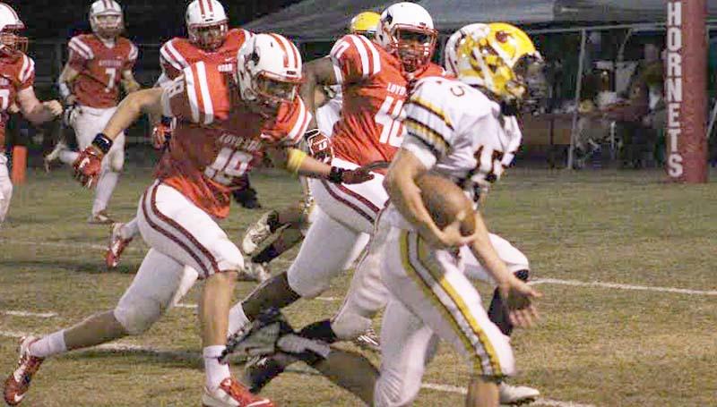 Daily Leader / Patty Emfinger / Enterprise quarterback Zach Hodges (15) rushes the ball as Loyd Star's defenders Konner Allen (18) and Avery Leggett (40) hustles to make the stop Friday night.