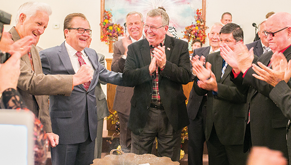 Photos by Kaitlin Mullins Rev. David Tipton (left) and Jack Rutland, senior vice president of State Bank in Brookhaven (center), surrounded by other local Pentecostal leaders, join to burn the note for the $23,000 loan balance on the First United Pentecostal Church of Wesson, which was paid in full as its founding pastor Rev. Lloyd Thompson's last wish.