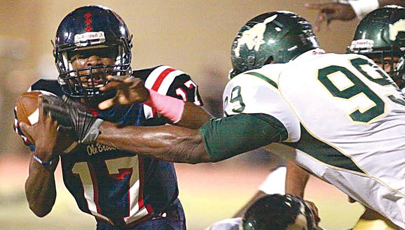 Daily Leader / Jonathon Alford / Brookhaven's freshmen quarterback Sevante Quinn (17) looks to get off a quick pass as West Jones defender Tyone Clemons (99) leaps in to record a sack Friday night at King Field.