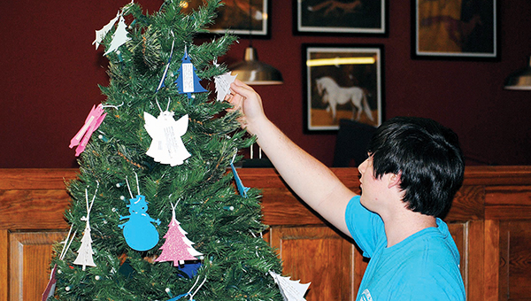 Aaron Paden / Jesse Freeman checks out an ornament at Fox's Pizza Thursday. Ornaments have individual children's needs and wishes on the back, with a short form for potential sponsors. Instruction sheets for participants sit next to the tree.