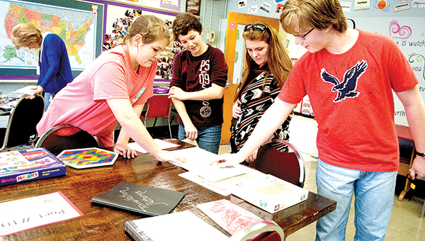 Photo by Julia Miller Lainey Brown (left) and Dylan Becker (right) show Nicole Ready (second from right) the fastest people have put together the puzzle during Lipsey's Cruise through Quest Wednesday. Ready was shown around the ports by her son, Ben Ready (second from left).