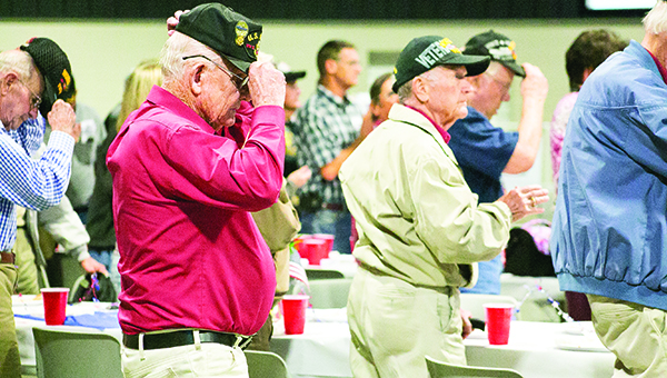 Photo by Kaitlin Mullins / Local veterans replace their caps after the National Anthem during the Veteran's Day Celebration at the Lincoln Civic Center Tuesday night.