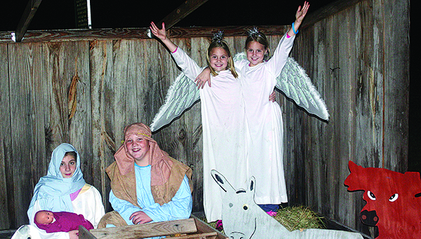 Photo by Aaron Paden / Mary, portrayed by Emily Douglas, and Joseph, portrayed by Eli Cupit, sit around the manger with Lillie and Sadie Cupit as angels in the background during last years live nativity scene.