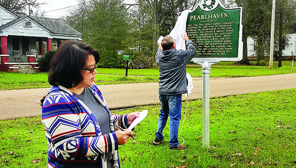 """Photo by Josh Rich / Tammie Brewer (left) reads wording from the Pearlhaven Historical Marker to the crowd while her husband, Dennis, removes the sign's covering Wednesday morning. The sign reads, """"In 1899, the Pearl River Lumber Company established the mill town of Pearlhaven. Pearlhaven was incorporated in 1901 with 310 residents, who elected a mayor, board of aldermen, and marshal the same year. The mill town included a hotel, three churches, a hospital, school and 235 employee houses, plus a standard gauge railroad. By 1903, the population grew to more than 1,000. When the company was sold in 1905, the mill property and houses were auctioned off, and Pearlhaven was annexed into Brookhaven in 1912."""""""