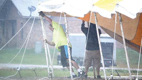 Photo by Luke Horton/ Two men work in the rain to erect a large fireworks tent on Dunn-Ratcliff Road Tuesday morning. Wet weather is expected to continue through Wednesday morning. See page 3 for a two-day forecast.