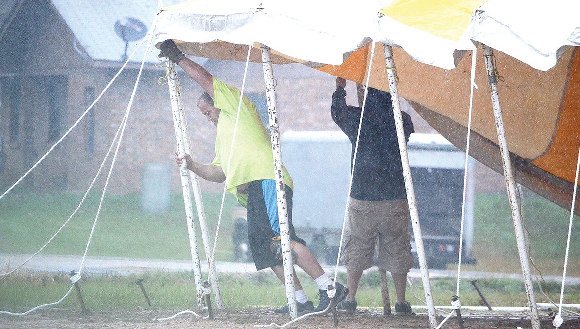 Photo by Luke Horton Two men work in the rain to erect a large fireworks tent on Dunn-Ratcliff Road Tuesday morning. Wet weather is expected to continue through Wednesday morning